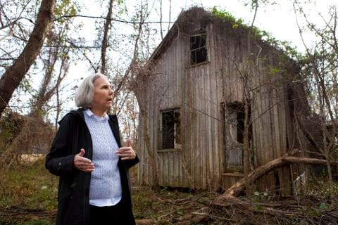 Older woman standing in front of a broken down wood house structure.